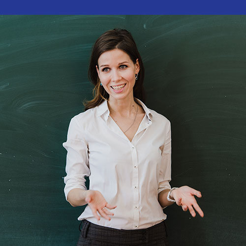 Photo of an adult white woman in a classroom holding her hands out and smiling.