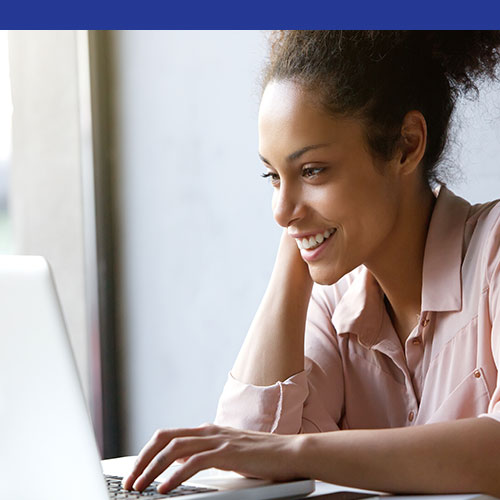 Photo of a smiling young black woman using her laptop computer