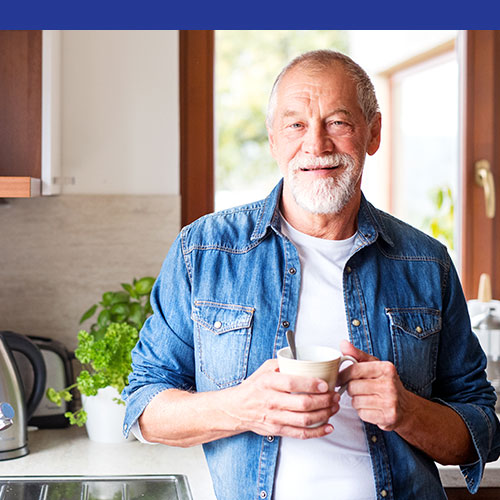 Photo of a smiling older white man holding a cup of coffee at home